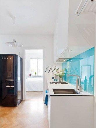 整体白色的厨房空间里,大量的单一色彩未免显得过于空洞和寡淡,而背景墙上小范围地运用淡蓝色玻璃进行搭配,让此墙面一跃成为视线的焦点
