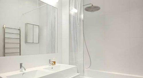 从墙壁到地面,从洁具到配件,纯白色的卫浴间如一尘不染的禁地。白色的浴室柜肩负着整个空间的收纳工作,上方安装双人洗面盆让这个卫浴间小而实用
