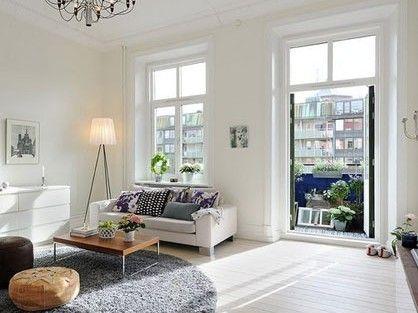 客厅选用了白色的墙面和沙发,然后配以不同色彩的软装饰,靠包、坐凳、盆栽等;还有沙发边的落地灯有着时尚的造型